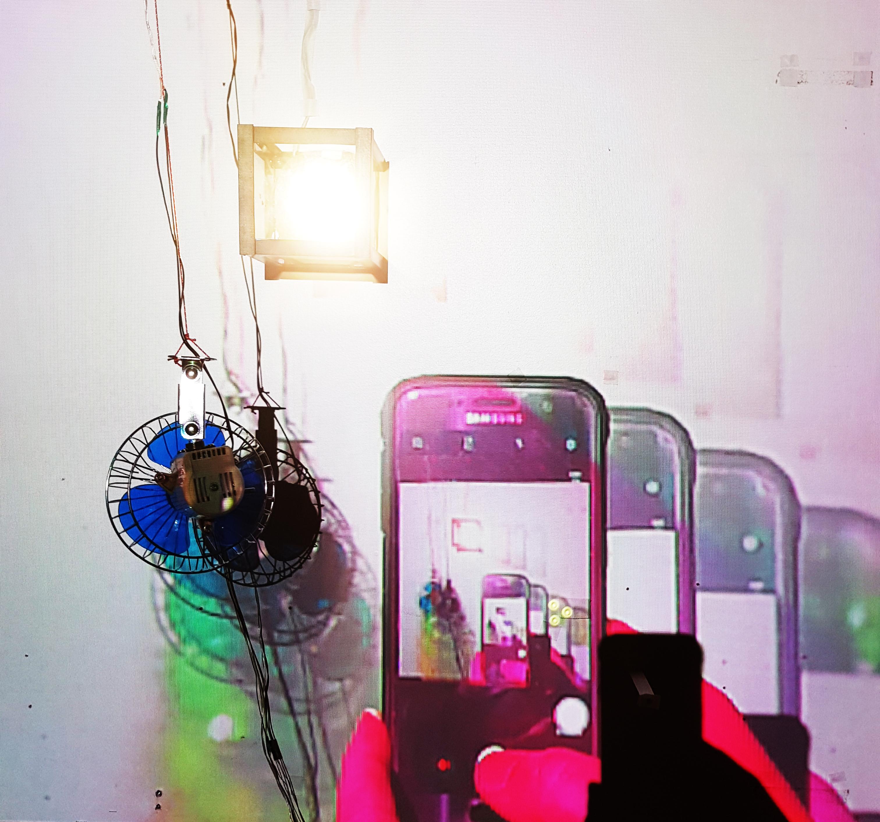 """Diminishing Returns (2019) Autonominen kineettinen videoinstallaatio liikkeestä ja kuvan muistosta. Monitaide / kineettinen installaatio / livevideo / XR. Diminishing Returns on analoginen seka-/monitaideteos/installaatio. Se ei asettaudu täysin minkään perinteisen videoteoksen tai installaation raameihin. Se on samalla analoginen/fyysisessä maailmassa oleva installaatio kuin """"kuvan maailmassa"""" oleva videoteos ja muunneltua todellisuutta.  Diminishing Returns ei myöskään ole nauhoite, vaan video/kuva tapahtuu ja luodaan """"tässä ja nyt"""", tilassa ja hetkessä jolloin katsoja teosta havainnoi. Ympäristö, tila, vallitseva valo, kaikki vaikuttavat teokseen. Katsoja itse voi halutessaan asettua teoksen seinän eteen ja päätyä hetkellisesti osaksi teosta, kunnes kuvan muisto pyyhkiytyy pois seinältä.  Diminishing Returns on alati muuttuva ja ei koskaan toistu samalla lailla kahta kertaa. Se elää omaa elämää tilassa, ajassa, varioiden, värähdellen ja muuttuen."""